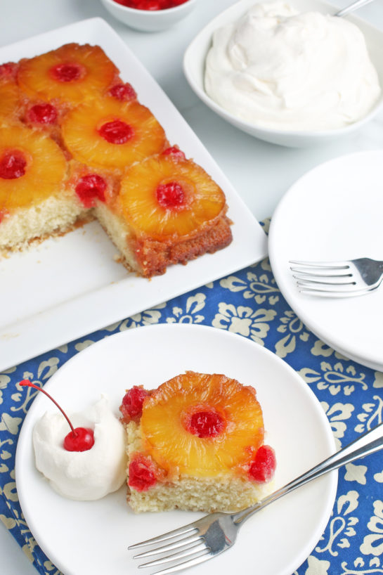 Another view of a slice of the upside down cake recipe on a plate, with whipped cream and fruit!