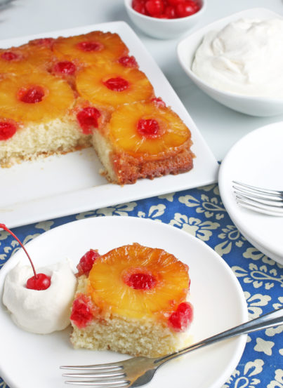 This photo shows us a slice of the pineapple upside down cake from scratch with the rest of the beautiful cake in the background.