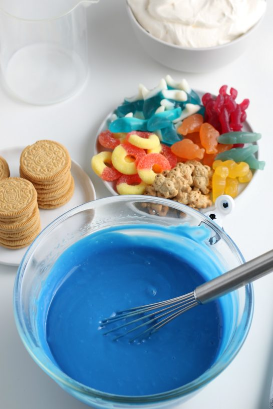 Adding the blue jello mix to the bowl to make beach sand pudding cups recipe