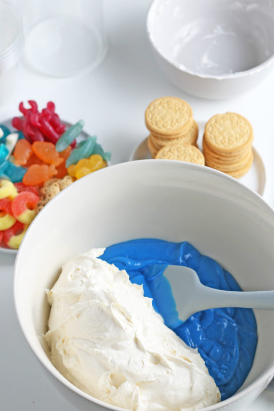 Adding the whipped topping to the blue Jello to the bowl to make beach sand pudding cups recipe