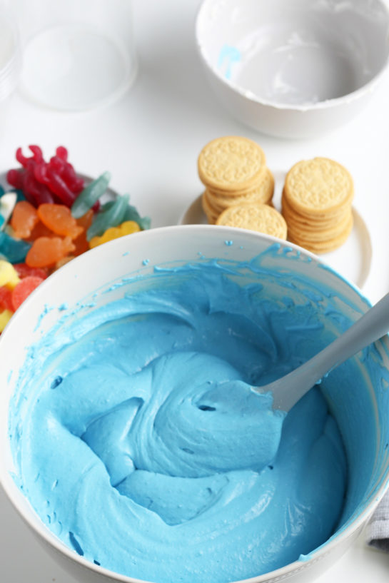Mixing together the blue jello and whipped topping to make this beach sand pudding cups recipe
