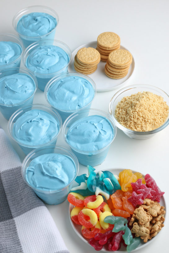 Pouring the blue jello mix into the plastic cups for the beach sand pudding cups recipe