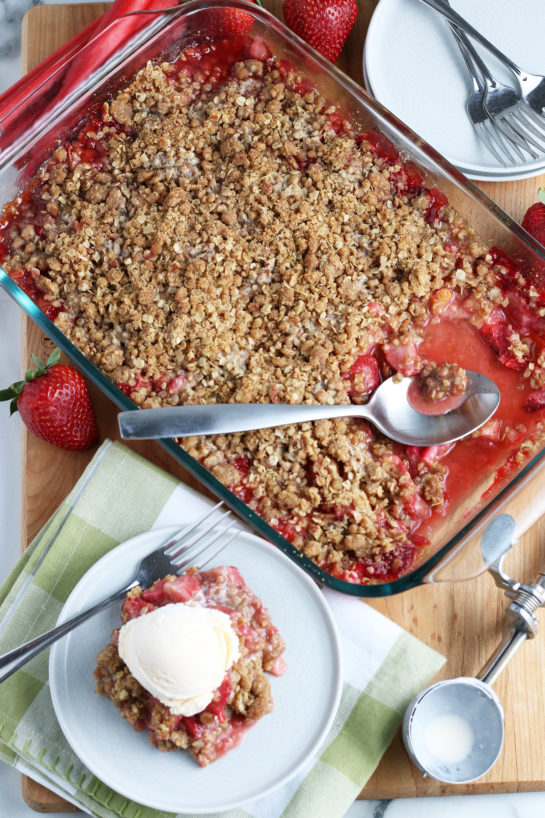 Overhead shot of Strawberry & Rhubarb crisp recipe finished in the pan and out of the oven and plated with a scoop of vanilla ice cream on top.