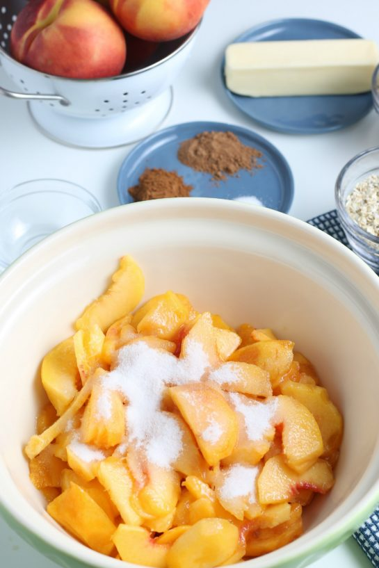 Adding the sugar to the peaches to make the fresh peach crisp recipe