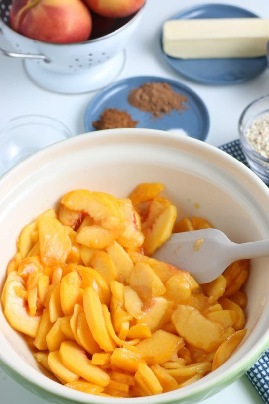 Stirring together the ingredients with the sliced peaches for the Fresh Peach Crisp recipe
