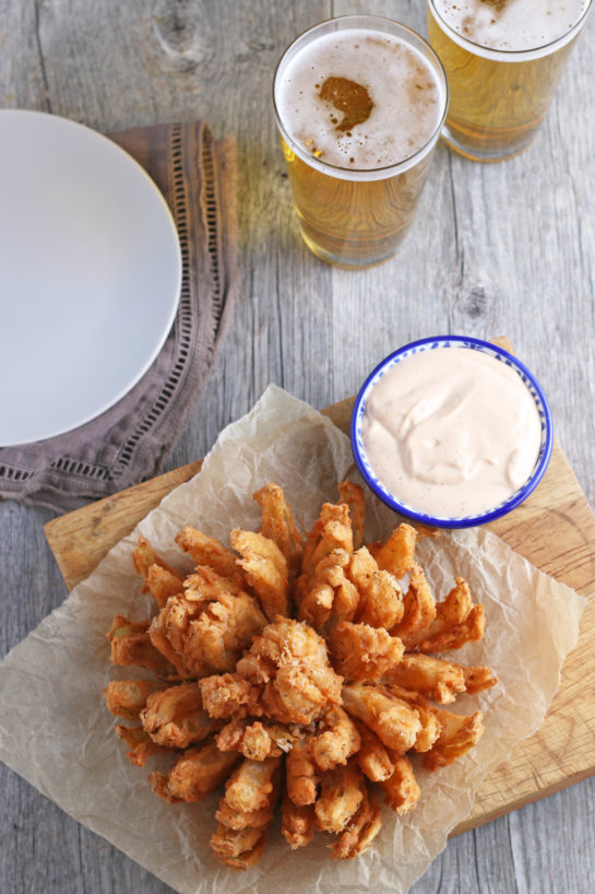 Overhead shot of the Fried Blooming Onion with a homemade dipping sauce is the ultimate appetizer recipe. Grab a sweet onion and turn it into a, incredibly delicious appetizer!