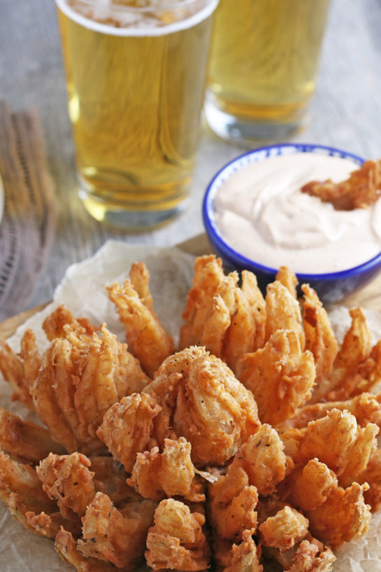 Deep-Fried Blooming Onion with a homemade dipping sauce is the ultimate appetizer recipe. Grab a sweet onion and turn it into a, incredible delicious snack!