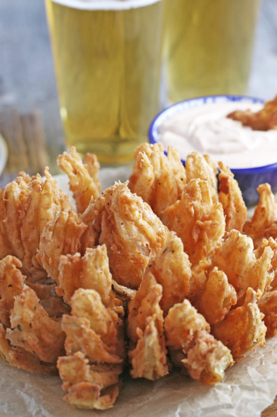 Close-up shot of Fried Blooming Onion with a homemade dipping sauce is the ultimate appetizer recipe. Grab a sweet onion and turn it into a, incredibly delicious appetizer!