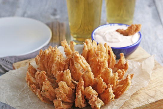 Fried Blooming Onion with a homemade dipping sauce is the ultimate appetizer recipe. Grab a sweet onion and turn it into a, incredibly delicious appetizer!