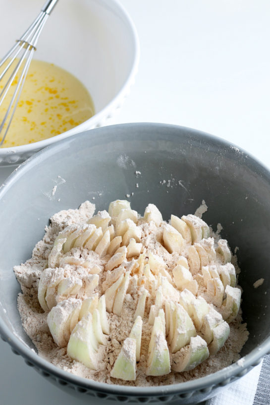 Dipping the onion in the batter for the blooming onion recipe