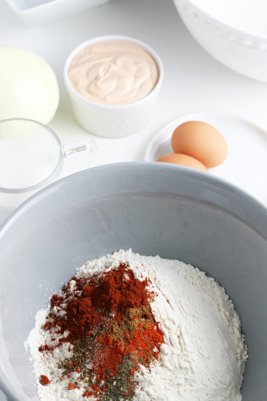 Adding the dry ingredients needed to make fried blooming onion recipe