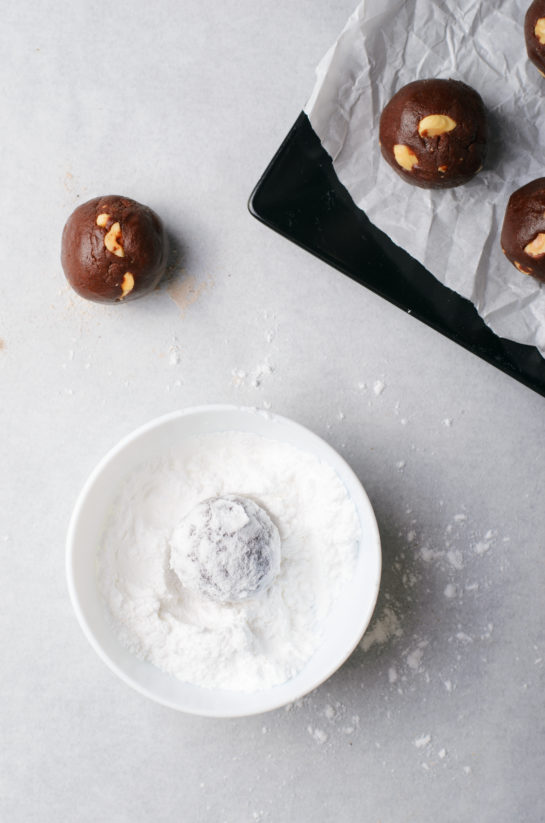 Rolling the cookies in powdered sugar for the chocolate hazelnut crinkle cookies recipe