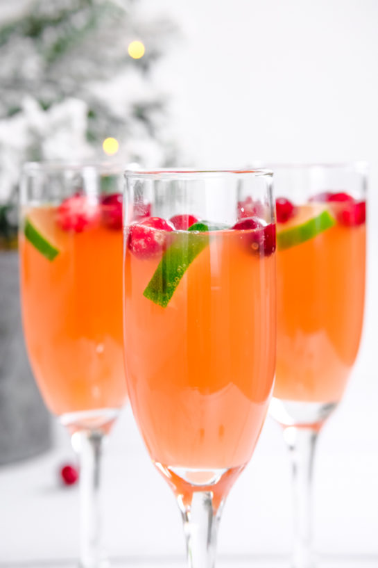 Close-up shot of the three holiday mimosas recipe with cranberries as garnish