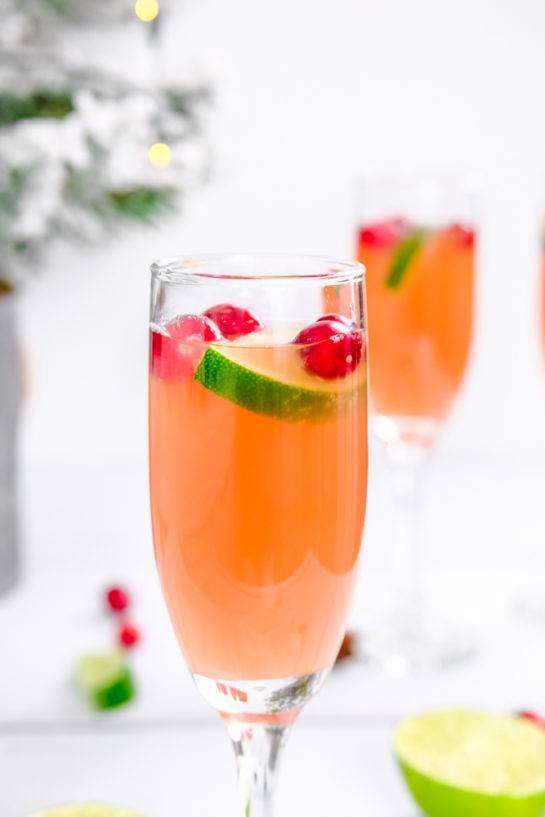 Close-up shot of one of the holiday mimosas recipe with cranberries and lime as garnish