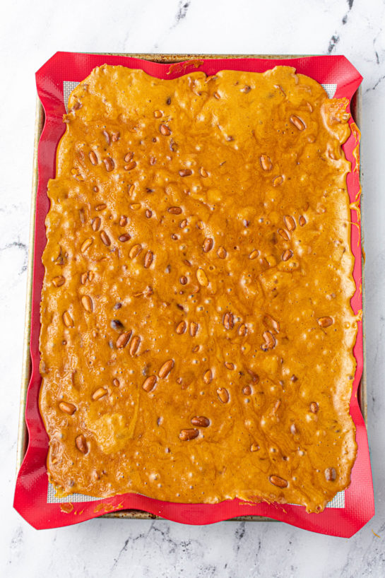 Spreading the mixture on the baking pan to make the Microwave Peanut Brittle recipe