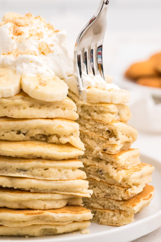 Cutting open the Banana Pudding Pancakes that are flavorful enough you don't even need the syrup! They are a quick and easy breakfast or brunch recipe you will love!