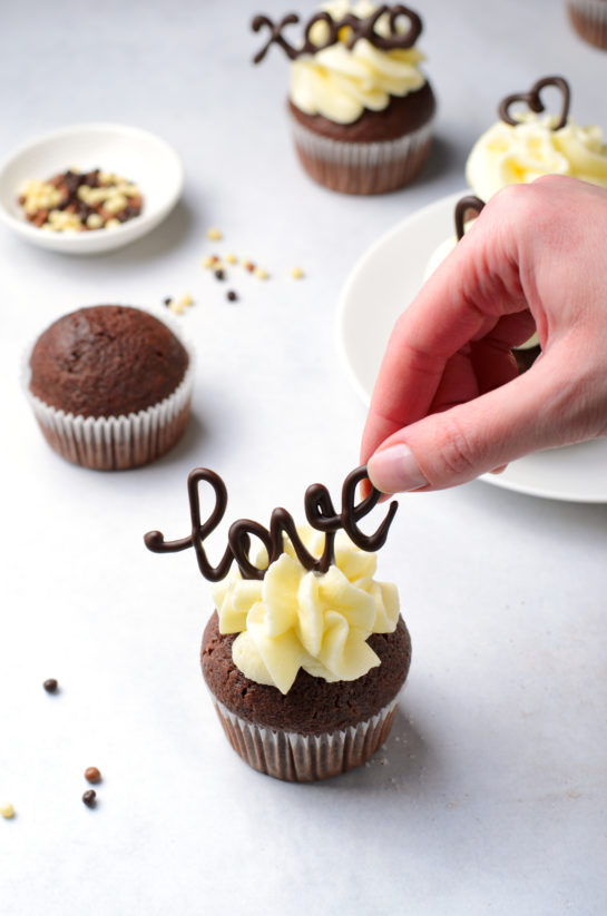 Placing the chocolate words on top for the Valentine's Day Lover's Chocolate Cupcakes