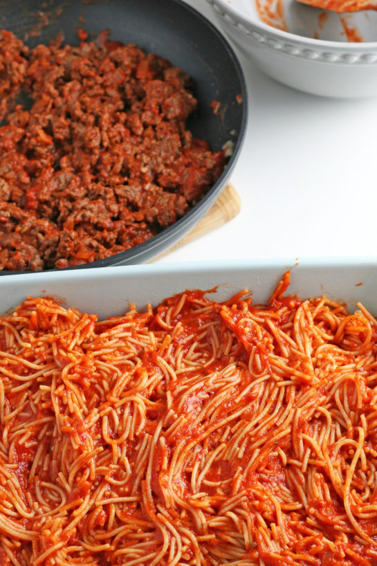The first layer that goes into our baked spaghetti recipe is the pasta with sauce.