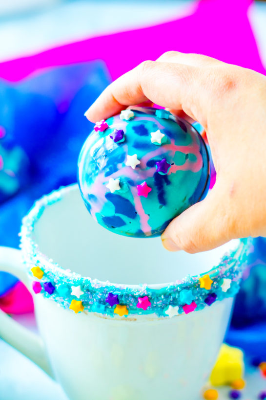 Galaxy Hot Chocolate Bombs are fun, colorful chocolate orbs filled with hot cocoa mix, marshmallows, and sprinkles. This recipe for hot chocolate bombs is an over-the-top way to level up your hot chocolate game, especially for a party!