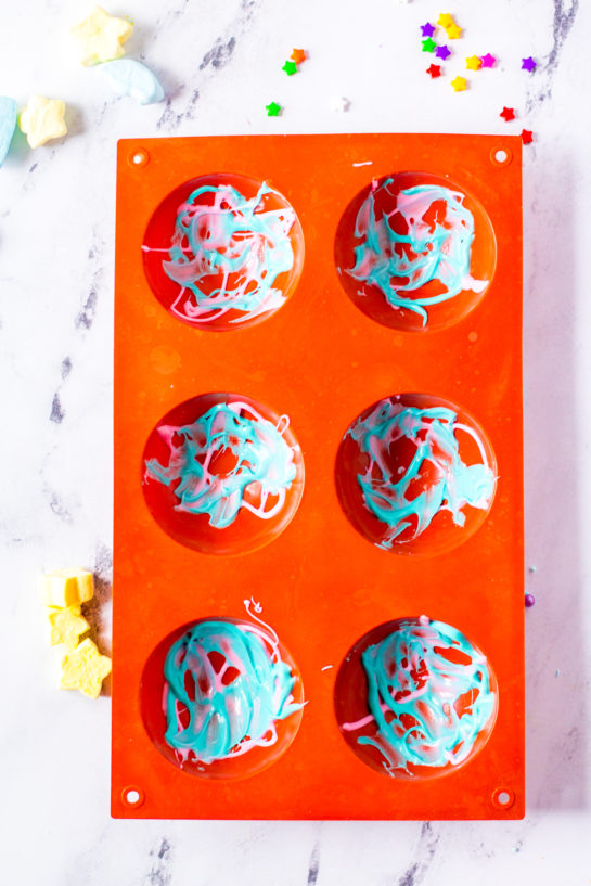 Overheard shot of the silicone molds with the blue and pink melted chocolate for the Galaxy Hot Chocolate Bombs recipe