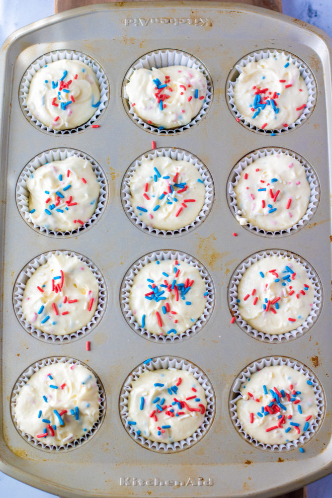Red, White, and Blue Mini Cheesecakes Recipe ready to go in the oven with the sprinkles on top