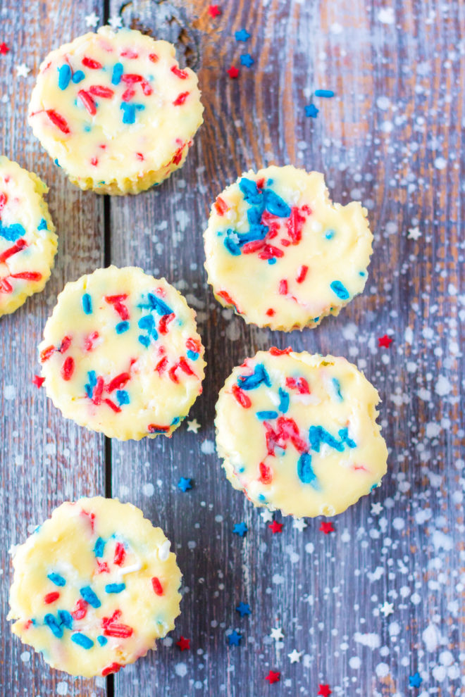 Red, White, and Blue Mini Cheesecakes recipelayered with a Golden Oreo crust and creamy tangy cheesecake. Top with sprinkles and whipped cream for the perfect dessert for 4th of July!