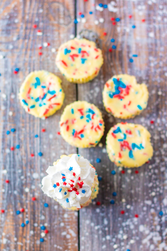 Red, White, and Blue Mini Cheesecakes recipelayered with a Golden Oreo crust and creamy tangy cheesecake. Top with sprinkles and whipped cream for the perfect patriotic dessert for Memorial Day or 4th of July!
