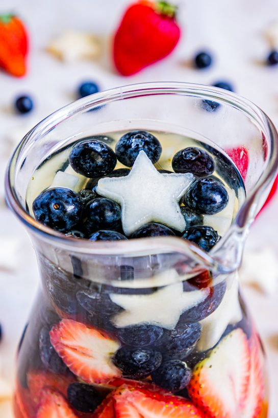 Close-up of my Patriotic Sangria recipe this summer to enjoy a cocktail while beating the heat at the same time! With fresh blueberries, strawberries, white grape juice, brandy, and wine, it's perfect for Flag Day, 4th of July or Memorial Day!