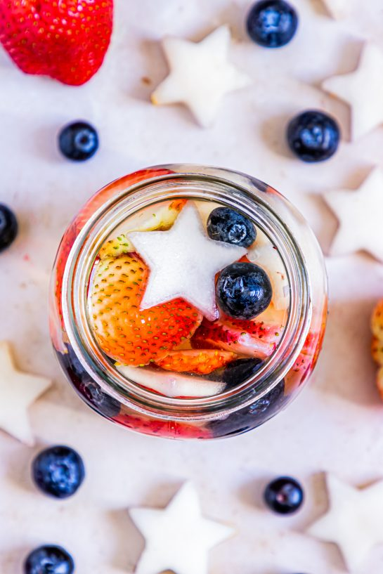 Overhead shot of my Patriotic Sangria recipe to enjoy a cocktail while beating the heat at the same time! With fresh blueberries, strawberries, white grape juice, brandy, and wine, it's perfect for 4th of July or Memorial Day!