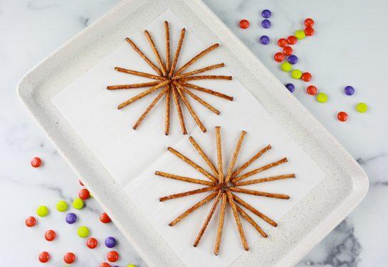 Arranging the pretzel sticks to make the Halloween Chocolate Pretzel Spider Webs