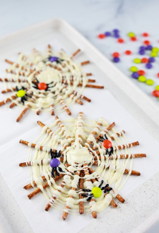 Spooky Halloween Chocolate Pretzel Spider Webs are a fun sweet & salty dessert recipe to serve for a children's or adult Halloween party! They are easy to make and look great on your party table!