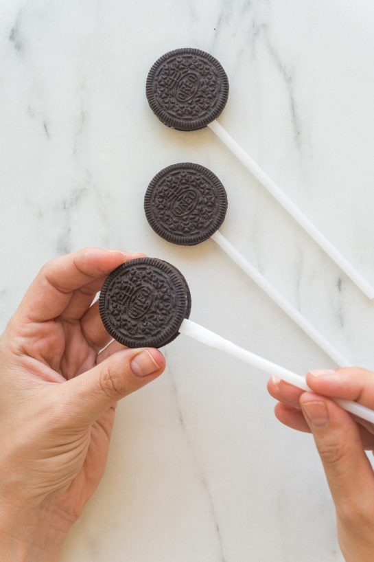Inserting the popsicle sticks to make the Mummy Oreo Pops recipe